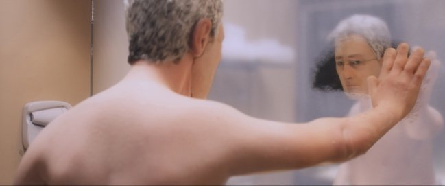 David Thewlis' Michael examines his joints in a hotel mirror. Courtesy of Paramount Pictures