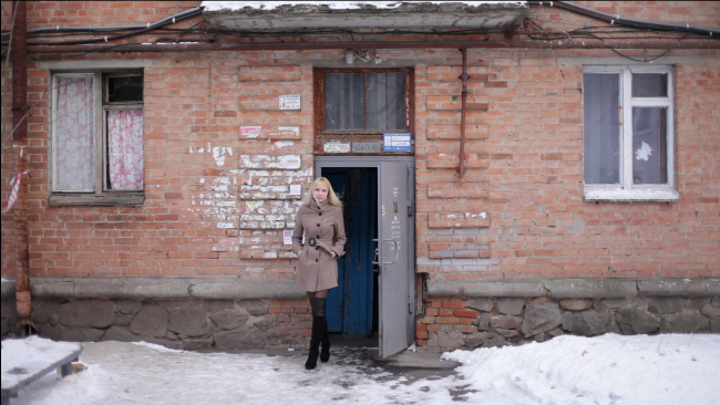 Mail-order bride Inna stands in front of her family home in snowy Ukraine.