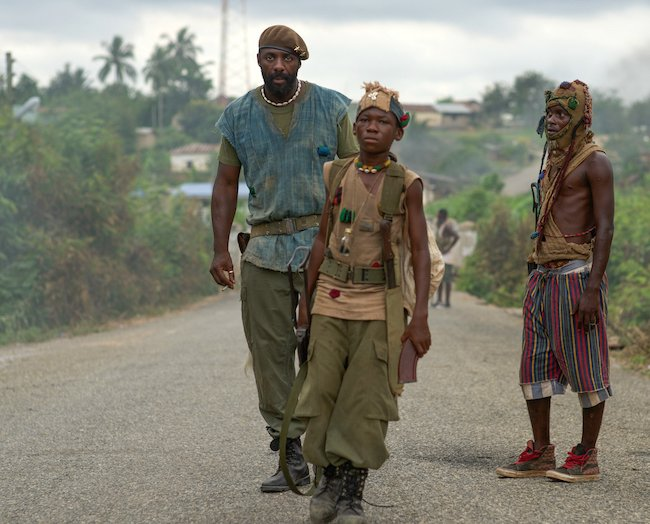 Agu (Abraham Attah) and the Commandant (Idris Elba) march through an unnamed African country.