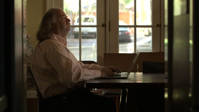 Jonathan Gold writing at his home office