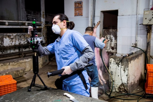 """Dennis films inside a Mexican pig slaughterhouse with a prototype virtual reality camera in December 2015, for his film """"Factory Farm"""""""