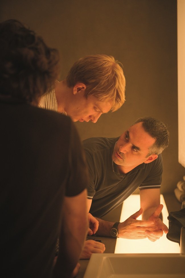 Gleeson and Garland (background) discuss a scene on the set of Ex Machina