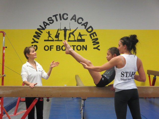 Ferraro assists a young gymnast at her gym.