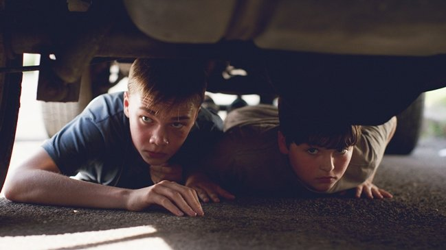 Jack (Charlie Plummer) and Ben (Cory Nichols) hide under a car to avoid Shane, the vicious local bully. Photograph by Brandon Roots