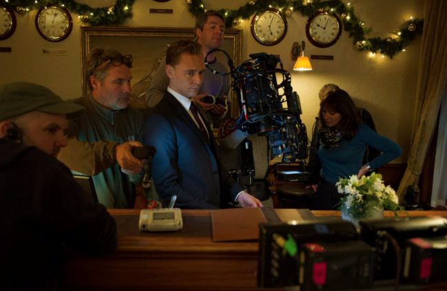 Tom Hiddleston (center) on the set of The Night Manager, with Susanne Bier (background, right).