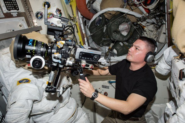 NASA astronaut Kjell Lindgren prepares the IMAX® camera over and empty space suite for an upcoming shoot onboard the International Space Station